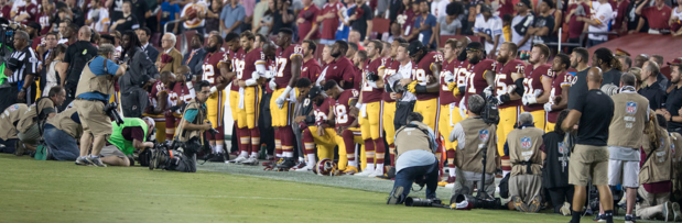 Mix of Redskin players kneeling and standing for our anthem. -- Google Common License
