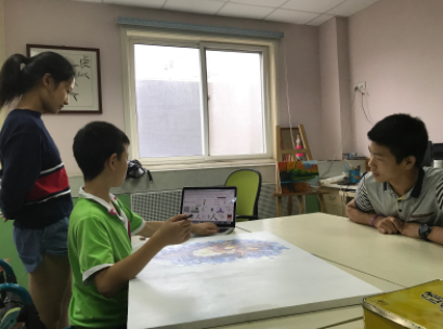 Melody supervises and assists students at an orphanage with their artwork.